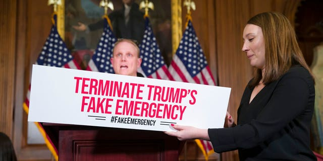 An aide places a placard on the podium, as a journalist does a sound check, before a media availability about a resolution to block President Donald Trump's emergency border security declaration on Capitol Hill, Monday, Feb. 25, 2019 in Washington.  (AP Photo/Alex Brandon)