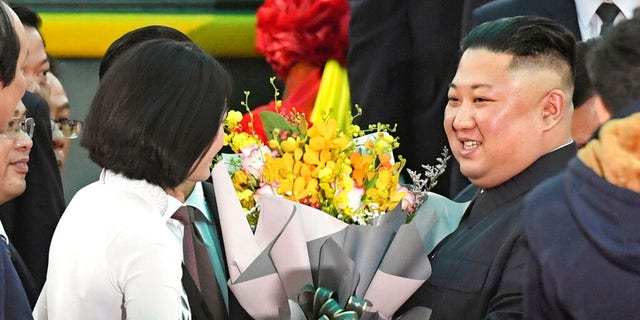 North Korean leader Kim Jong Un, right, receives bouquets on his arrival at the Dong Dang railway station in Dong Dang, a Vietnamese border town Tuesday.