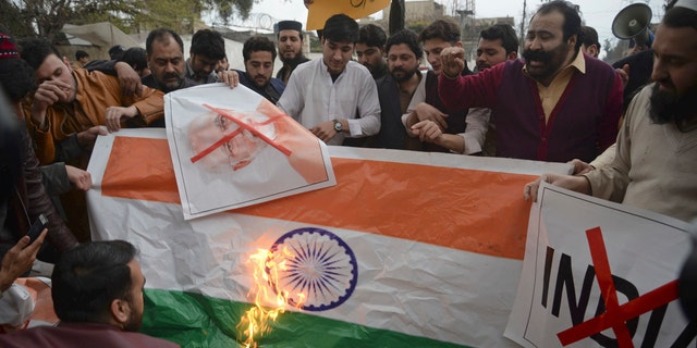 """Pakistani protesters burn a representation of an Indian flag during an anti-Indian rally in Peshawar, Pakistan, Tuesday, Feb. 26, 2019. Pakistan said India launched an airstrike on its territory early Tuesday that caused no casualties, while India said it targeted a terrorist training camp in a pre-emptive strike that killed a """"very large number"""" of militants."""