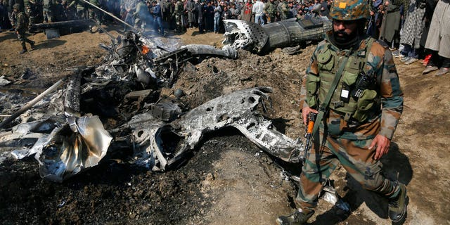 An Indian army soldier walks past the wreckage of an Indian aircraft after it crashed in Budgam area, outskirts of Srinagar, Indian controlled Kashmir, Wednesday, Feb.27, 2019.