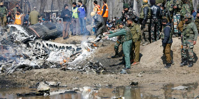 An Indian Air Force officer along with others inspects the wreckage of an Indian aircraft after it crashed in Indian controlled Kashmir. This crash is the latest development as tensions rise betwen Pakistan and India over Kashmir.
