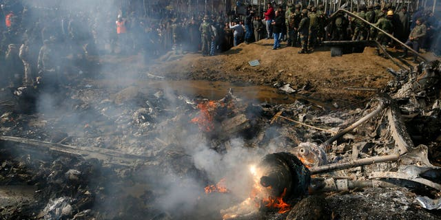 Kashmiri villagers and Indian army soldiers gather near the wreckage of an Indian aircraft after it crashed in Indian controlled Kashmir. (AP Photo/Mukhtar Khan)
