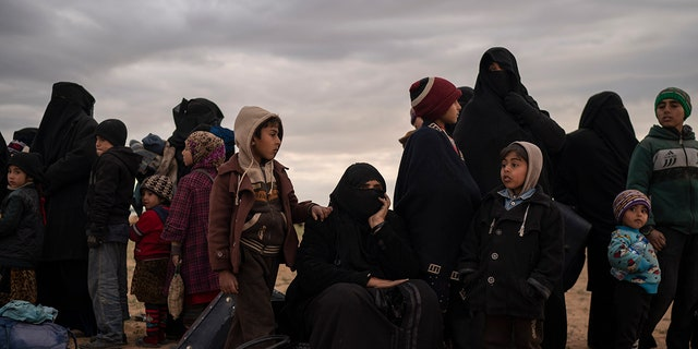 Women and children evacuated out of the last territory held by Islamic State militants wait to be screened by U.S.-backed Syrian Democratic Forces (SDF) in the desert outside Baghouz, Syria, Wednesday, Feb. 27, 2019.