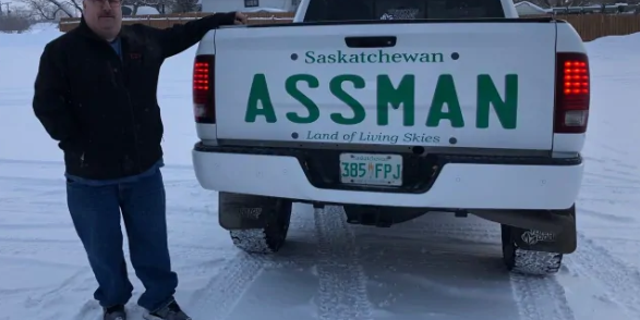 David Assman standing next to his pickup truck with a decal bearing his last name.