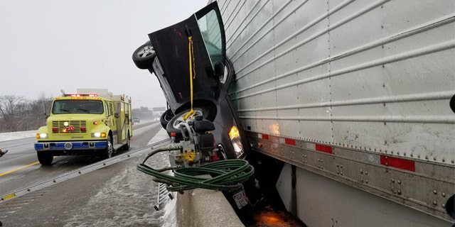 An Ohio fire department posted photos online of a car that was pinned between a highway barrier and a semi-truck.