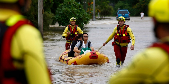 In this Sunday, Feb. 3, 2019, photo, Queensland Fire and Emergency Services crew members use an inflatable boat to pull residents through floodwaters at Hermit Park in Townsville, Australia.
