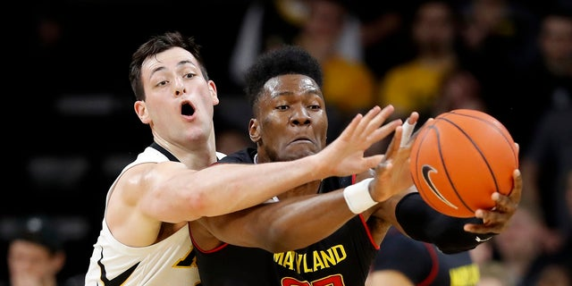 Iowa forward Ryan Kriener, left, tries to steal the ball from Maryland forward Bruno Fernando during the second half of an NCAA college basketball game Tuesday, Feb. 19, 2019, in Iowa City, Iowa.