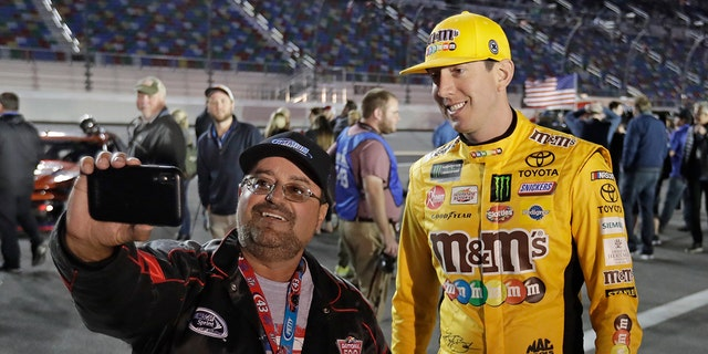 Kyle Busch, right, poses for a selfie photo with a race fan before the first of two qualifying auto races for the NASCAR Daytona 500 at Daytona International Speedway, Thursday, in Daytona Beach, Fla. (AP Photo/John Raoux)