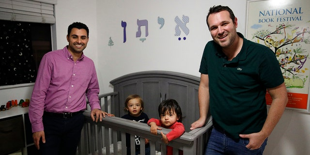 FILE - In the Tuesday, Jan. 23, 2018 file photo, Elad Dvash-Banks, left, and his partner, Andrew, pose for photos with their twin sons, Ethan, center right, and Aiden in their apartment in Los Angeles. (AP Photo/Jae C. Hong, File)