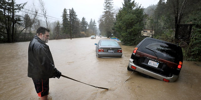 Tim Russell of Guerneville attempts to pull a motorist from Armstrong Woods Road after it became inundated in Guerneville, Calif., Tuesday, Feb. 26, 2019.