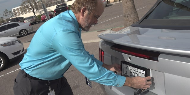 ADOT spokesman, Doug Nick, showing Fox News where the digital license plates would be placed, in the same location as the traditional metal plates