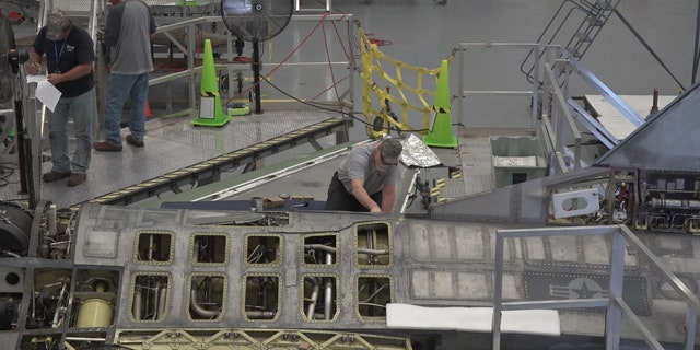 "A ""boneyard wrangler"" working on a fighter jet to refurbish for Boeing's autonomous flying testing."