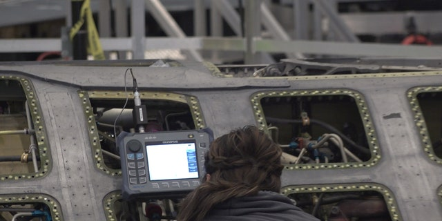 "A ""boneyard wrangler"" working on a fighter jet to refurbish."