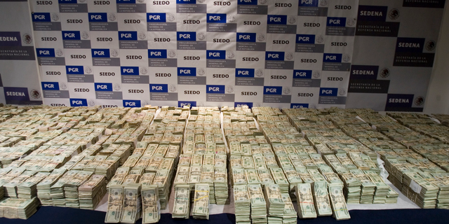 FILE - In this Sept. 18, 2008, file photo, cash seized by Mexico's Army, which according to the Defense Department was seized on Sept. 14 from the Sinaloa drug cartel and is displayed to the press in Mexico City. Federal authorities have said they want to go after an estimated $14 billion fortune for the Mexican drug lord known as El Chapo, who was head of the cartel. (AP Photo/Eduardo Verdugo, File)