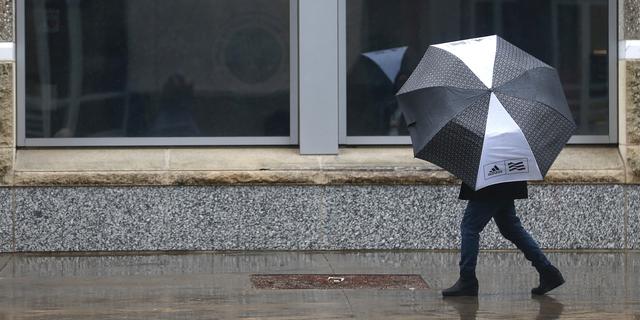 A person huddles under an umbrella as rain falls in Sacramento, Calif., Tuesday, Feb. 26, 2019. (AP Photo/Rich Pedroncelli)