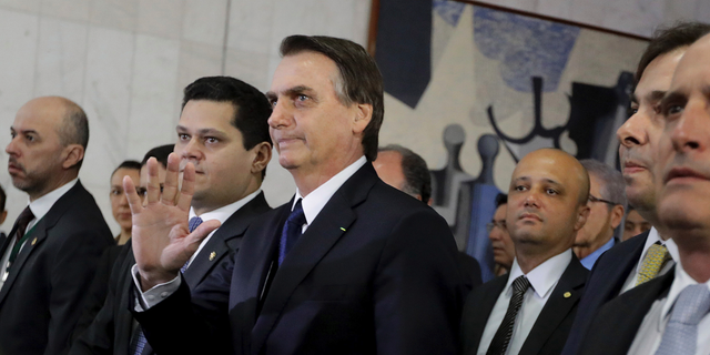Brazil's President Jair Bolsonaro, center, arrives at the National Congress to deliver a proposal to overhaul Brazil's pension system, in Brasilia, Brazil, Wednesday, Feb. 20, 2019. Lawmakers received this week an anti-crime bill and a proposal to overhaul Brazil's pension system, the government's flagship reform. (AP Photo/Lucio Tavora)