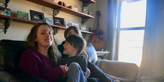"""In this 2019 photo provided by Americans United for Separation of Church and State, Aimee Maddonna smiles while sitting with her children at her home in Simpsonville, S.C. The South Carolina mother has sued both the state and federal government, saying she's a victim of religious discrimination on the part of a federally funded foster-care agency that turned her down because of her Catholic faith. Maddonna says the agency in 2014 initially encouraged her to become a foster parent but cut off ties once realizing that she is Catholic and not a """"born-again"""" Christian, as the agency's internal rules require. (Courtesy of Aimee Maddonna/Americans United for Separation of Church and State via AP)"""