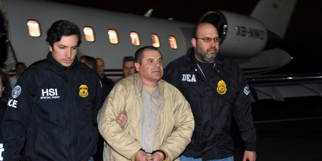 """FILE - In this Jan. 19, 2017 file photo provided U.S. law enforcement, authorities escort Joaquin """"El Chapo"""" Guzman, center, from a plane to a waiting caravan of SUVs at Long Island MacArthur Airport in Ronkonkoma, N.Y. The notorious Mexican drug lord was convicted of drug-trafficking charges, Tuesday, Feb. 12 2019, in federal court in New York. (U.S. law enforcement via AP, File)"""