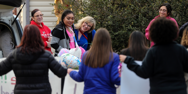 In this Jan. 31, 2019 photo, Zei Uwadia, second from left, is greeted by supporters as she returns to her Wichita, Kan., home, after spending the last 457 days at Children's Mercy hospital in Kansas City following her collapse from a lung condition. Uwadia died in her home on Tuesday, Feb. 12, 2019, her mother said. She was 17. (Travis Heying/The Wichita Eagle via AP)