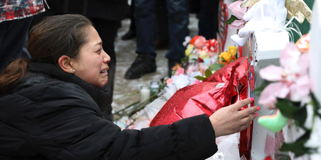 One of victim Vicente Juarez's daughter Diana Juarez cries as she touch a cross at a makeshift memorial Sunday, Feb. 17, 2019, in Aurora, Ill., near Henry Pratt Co. manufacturing company where several were killed on Friday. Authorities say an initial background check five years ago failed to flag an out-of-state felony conviction that would have prevented a man from buying the gun he used in the mass shooting in Aurora. (AP Photo/Nam Y. Huh)