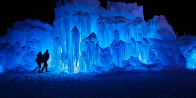In this Saturday, Jan. 26, 2019 photo, a couple heads towards an entrance to a cavern at Ice Castles in North Woodstock, N.H. A team starts building massive walls in December to create a spectacular winter experience. (AP Photo/Robert F. Bukaty)