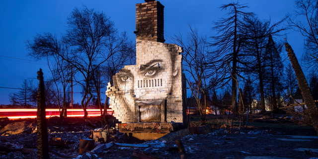 In this Feb. 8, 2019, photo, a mural by artist Shane Grammer adorns the chimney of a residence leveled by the Camp Fire in Paradise, Calif. Grammer says he painted murals throughout the fire-ravaged town to convey hope in the midst of destruction. In the 100 days since a wildfire nearly burned the town of Paradise off the map, the long recovery is just starting. Work crews have been cutting down trees and clearing burned-out lots, but Paradise is mostly a ghost town where survivors still dig for keepsakes in the foundations of their homes. (AP Photo/Noah Berger)