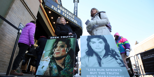 """Brenda Jenkyns and Catherine Van Tighem stand with signs outside of the premiere of the """"Leaving Neverland"""" documentary film at the Egyptian Theatre on Main Street during the 2019 Sundance Film Festival in Park City, Utah, on Jan. 25, 2019. (Photo by Danny Moloshok/Invision/AP, File)"""