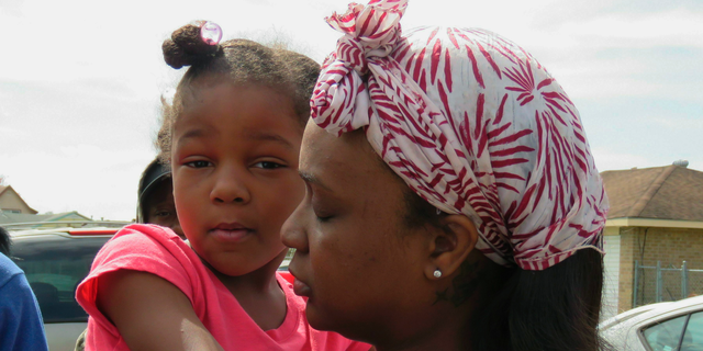 Markia Thomas, of Marrero, La., holds her daughter as she talks to reporters Thursday, Feb. 14, 2019, about the death of her 9-year-old son, Marquis Thomas Jr., the previous night. Marquis was accidentally shot in the head and killed Wednesday night when an 18-year-old cousin tried to get his gun away from the youngster, a Louisiana sheriff said. (AP Photo/Janet McConnaughey)
