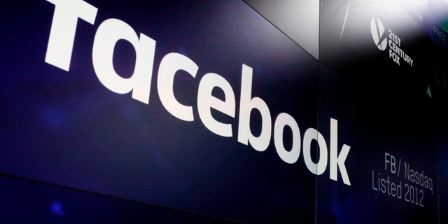 FILE- In this March 29, 2018, file photo, the logo for Facebook appears on screens at the Nasdaq MarketSite in New York's Times Square. (AP Photo/Richard Drew, File)