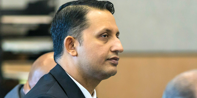 Former Palm Beach Gardens police officer Nouman Raja listens to defense attorney Scott Richardson give opening statements in Raja's trial, Tuesday, Feb. 26, 2019, in West Palm Beach, Fla. Raja is charged with the fatal 2015 shooting of a stranded black motorist, 31-year-old Corey Jones. (Lannis Waters/Palm Beach Post via AP, Pool)
