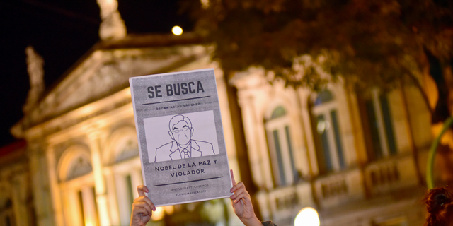 """A woman holds up a sign with a line drawing depicting Costa Rica's ex-President Oscar Arias and a message that reads in Spanish: """"WANTED: Oscar Arias Nobel Peace Prize laureate and Violator"""", during a protest by women activists under the slogan """"Yo te creo,"""" or """"I believe you,"""" in San Jose, Costa Rica, Friday Feb. 8, 2019. At least five women have accused Arias of actions ranging from unwelcome fondling or sexual innuendo to sexual assault. (AP Photo/Carlos Gonzalez)"""