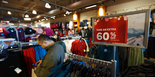 FILE- In this Dec. 24, 2018, photo a last-minute shopper scans his mobile device next to a sign marking discounts on coats at Columbia store as shoppers finish up their Christmas gift lists at the Outlet Malls in Castle Rock in Castle Rock, Colo. The On Thursday, Feb. 14, 2019, the Commerce Department releases U.S. retail sales data for December. (AP Photo/David Zalubowski, File)