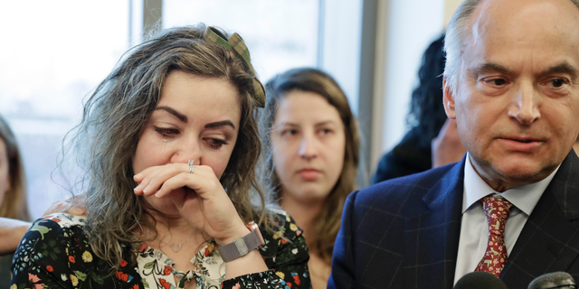 CORRECTS TO RECKLESS HOMICIDE, NOT CRIMINAL HOMICIDE- RaDonda Vaught, left, wipes away tears as her attorney, Peter Strianse, right, talks with reporters after a court hearing Wednesday, Feb. 20, 2019, in Nashville, Tenn. Vaught, a former nurse at Vanderbilt University Medical Center, is charged with reckless homicide after a medication error killed a patient. (AP Photo/Mark Humphrey)