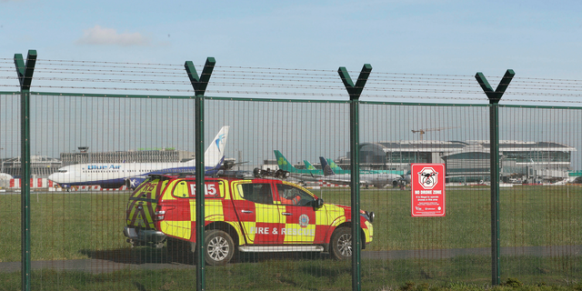 An emergency service vehicle by the perimeter fence after a confirmed drone sighting forced the temporary suspension of operations at Dublin Airport, Ireland, Thursday Feb. 21, 2019.  Flights at Dublin Airport were grounded for a short time Thursday, to ensure the safety and security of passengers after a confirmed drone sighting. (Nial Carson/PA via AP)