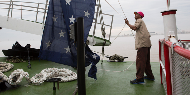"""FILE - In this March 15, 2015 file photo, Dwayne McCornick, a deck hand on the Natchez steamboat for 16 years, raises the Union Jack naval flag on the Mississippi River in New Orleans. After nearly 17 years, United States Navy warships will return to flying the Union Jack, replacing the First Navy Jack flown in the wake of the Sept. 11 attacks. News outlets report Chief of Naval Operations Adm. John Richardson issued an order Thursday, Feb. 21, 2019, calling for the blue banner with 50 white stars to return June 4 to commemorate World War II's Battle of Midway. The Navy's current maritime flag, the First Navy Jack, featured red and white stripes with a rattlesnake and the words """"Don't Tread On Me."""" (AP Photo/Samantha Kaplan, File)"""