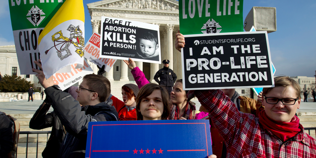 FILE - In this Friday, Jan. 18, 2019 file photo, anti-abortion activists protest outside of the U.S. Supreme Court, during the March for Life in Washington. (AP Photo/Jose Luis Magana)