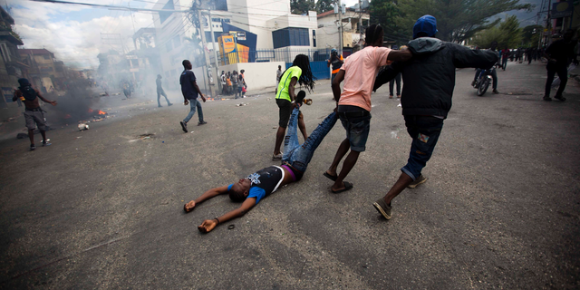 Demonstrators drag the body of a fellow protester toward police, as a form of protest after police shot into the crowd in which he died, during a demonstration demanding the resignation of Haitian President Jovenel Moise near the presidential palace in Port-au-Prince, Haiti, Tuesday, Feb. 12, 2019. Protesters are angry about skyrocketing inflation and the government's failure to prosecute embezzlement from a multi-billion Venezuelan program that sent discounted oil to Haiti. (AP Photo/Dieu Nalio Chery)