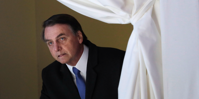 FILE - In this Jan. 22, 2019 file photo, Brazil's President Jair Bolsonaro enters the stage at the World Economic Forum, in Davos, Switzerland. Bolsonaro remains in the semi-intensive unit of a hospital in Sao Paulo with signs of a possible pneumonia infection, the Albert Einstein Hospital said in a statement Thursday, Feb. 7, 2019. (AP Photo/Markus Schreiber, File)