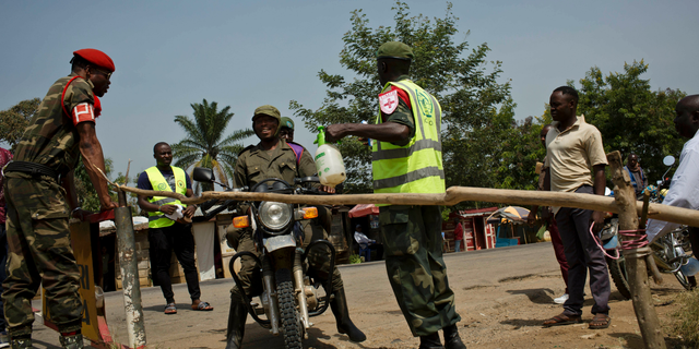 Two Congolese government soldiers have their feet and motorcycle tires sprayed with bleach as part of an Ebola containment programme on the road between Beni and Oicha, in Congo Friday, Feb. 1, 2019. The deadly Ebola outbreak in eastern Congo marked six months on Friday with officials noting a worrying number of confirmed cases linked to health centers.