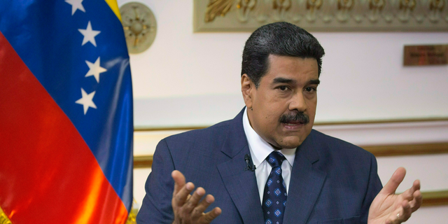 """FILE - In this Feb. 14, 2019 file photo, Venezuela's President Nicolas Maduro speaks during an interview at Miraflores presidential palace in Caracas, Venezuela. Maduro said Wednesday, Feb. 20, 2019, that 300 metric tons of high-cost medicines and aid was on its way from Russia.""""We're not beggars,"""" said Maduro. He insisted that Venezuela would pay for the aid and that it was coordinated with the support of United Nations' agencies. (AP Photo/Ariana Cubillos, File)"""
