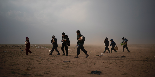 Children evacuated out of the last territory held by Islamic State militants walk at a screening center after collecting food, outside Baghouz, Syria, Tuesday, Feb. 26, 2019. Evacuations have continued amid a standoff between the militants and the U.S.-backed Syrian Democratic Forces (SDF). (AP Photo/Felipe Dana)