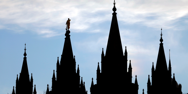 FILE- In this Jan. 3, 2018, file photo, the angel Moroni statue, silhouetted against the sky, sits atop the Salt Lake Temple at Temple Square in Salt Lake City. The Mormon church won't stand in the way of a proposal to ban gay conversion therapy for minors in its home base of Utah, a position that advocates heralded as a milestone in the conservative state. (AP Photo/Rick Bowmer, File)