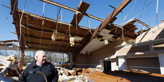 Pastor Steve Blaylock looks over the broken lumber, loose paneling, insulation, and destroyed pews in the First Pentecostal Church in Columbus, Miss., Sunday morning, Feb. 24, 2019 after a Saturday tornado. While no-one was injured during the storm, at least one person was killed in town among the shattered businesses and wrecked homes. (AP Photo/Rogelio V. Solis)