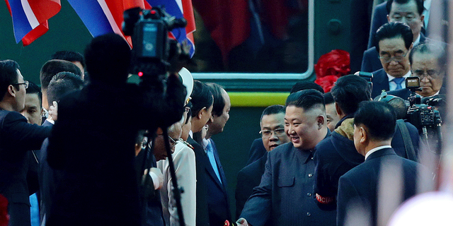 North Korean leader Kim Jong Un, center right, is welcomed upon arrival by train, back, in Dong Dang in Vietnamese border town Tuesday.