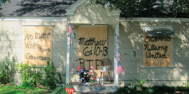 This Feb. 20, 2019 photos shows a makeshift memorial with flowers and candles that has been set up at the front door of a home in Houston where a couple who lived inside were killed during a Jan. 28 drug raid by Houston police. Friends of the Houston couple fatally shot by police during the drug raid of their home continue pushing back against claims the two were criminals. The FBI is investigating, and the officer who requested the search warrant was suspended. (AP Photo/Juan Lozano)