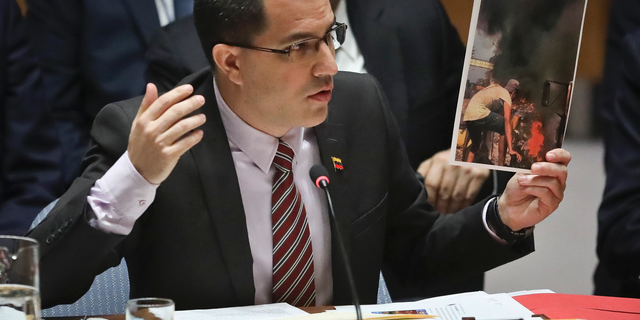 Venezuela Foreign Affairs Minister Jorge Arreaza shows picture he said represent opposition members initiating violence, during a meeting on Venezuela in the U.N. Security Council at U.N. headquarters, Tuesday Feb. 26, 2019. (AP Photo/Bebeto Matthews)