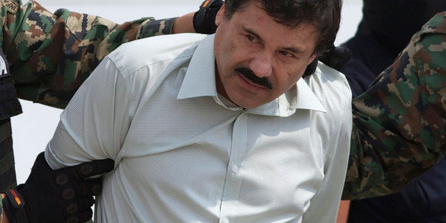 """This Feb. 22, 2014 file photo shows Joaquin """"El Chapo"""" Guzman, the head of Mexico's Sinaloa Cartel, being escorted to a helicopter in Mexico City following his capture in the beach resort town of Mazatlan."""