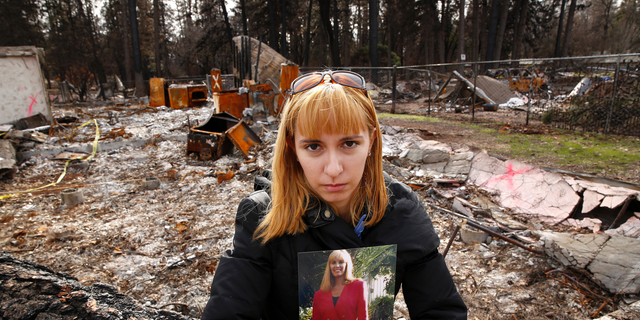 In this Thursday, Feb. 7, 2019 photo, Christina Taft, the daughter of Camp Fire victim Victoria Taft, poses with a photo of her mother, at the burned out ruins of the Paradise, Calif., home where she died last fall. Taft refused to leave. If the threat was real, authorities would order an evacuation, she told her daughter. Victoria Taft's remains were recovered from the ruins of her living room. (AP Photo/Rich Pedroncelli)