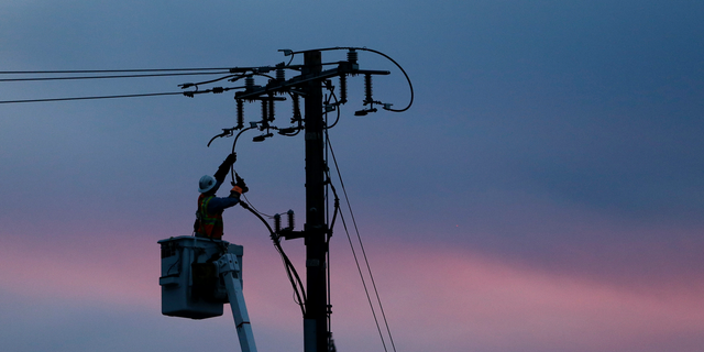 FILE - In this Nov. 26, 2018, file photo, a Pacific Gas & Electric lineman works to repair a power line in fire-ravaged Paradise, Calif. A U.S. judge who has berated Pacific Gas & Electric Co. for its role in wildfires in California is demanding more answers from the utility. In a court filing on Thursday, Feb. 14, 2019, Judge William Alsup asked PG&E whether it was in compliance with a state law that requires it to clear vegetation around electric lines. The judge also questioned a part of the utility's recently submitted wildfire mitigation plan. (AP Photo/Rich Pedroncelli, File)