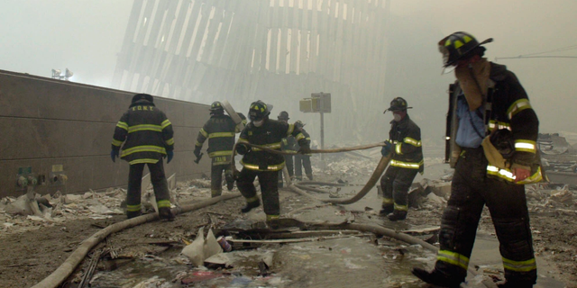 FILE - In this Sept. 11, 2001 file photo, with the skeleton of the World Trade Center twin towers in the background, New York City firefighters work amid debris on Cortlandt St. after the terrorist attacks. On Friday, Feb. 15, 2019, Rupa Bhattacharyya, the September 11th Victim Compensation Fund special master, announced that the compensation fund for victims of the Sept. 11, 2001 terror attacks will cut future payments by 50 to 70 percent because the fund is running out of money. (AP Photo/Mark Lennihan, File)